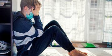 Depressed boy sitting next to window During quarantine in COVID-19 coronavirus